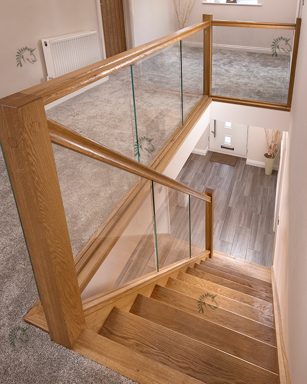 Recessed Vision glass balustrade with oak handrail and newel posts